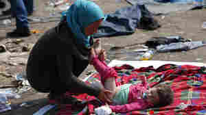 A migrant takes care of her baby at a collection point near the Serbian-Hungarian border in Roszke, Hungary, on Saturday.