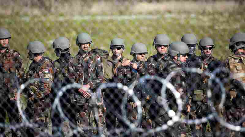 Soldiers stand by the border between Hungary and Serbia.