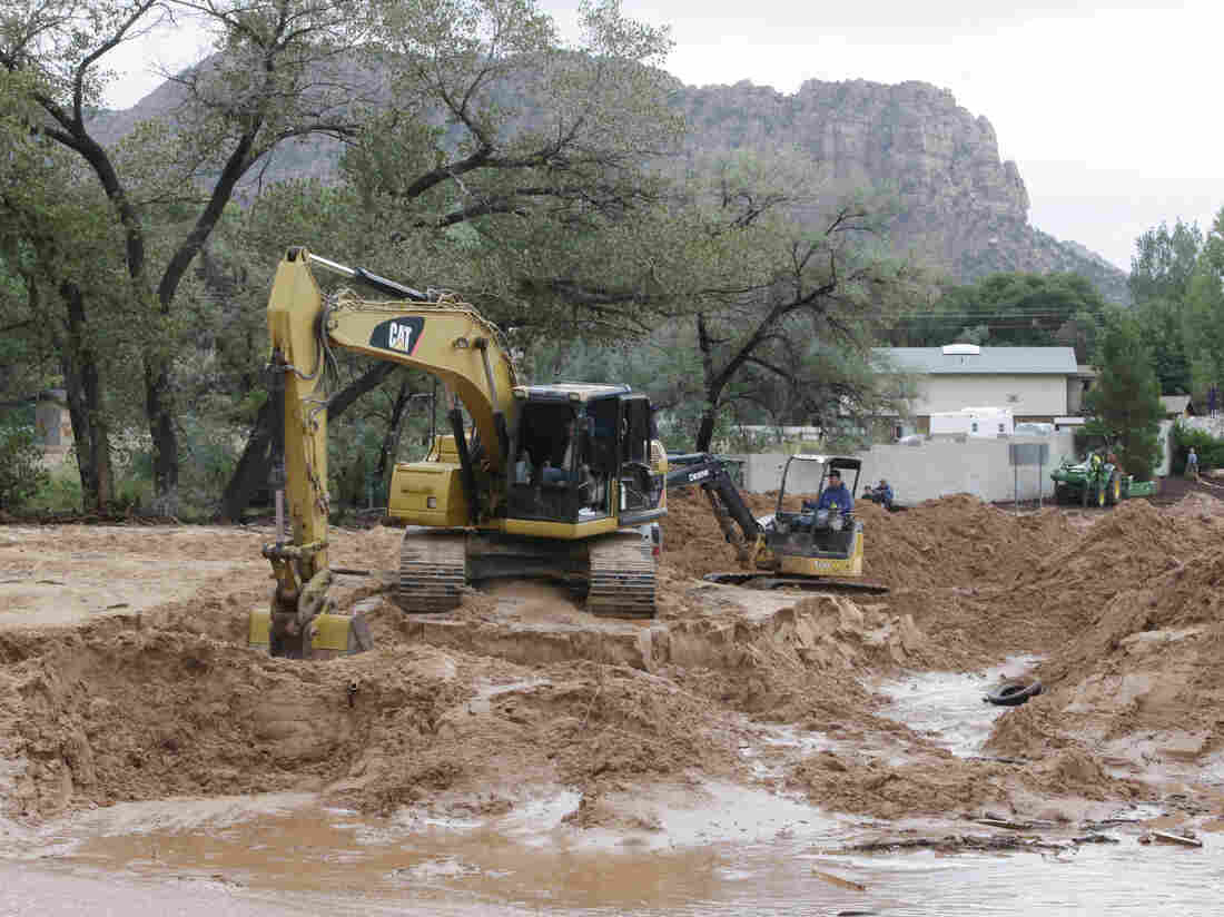Search crews clear mud and debris from a road following a flash flood Monday in Hildale, Utah.