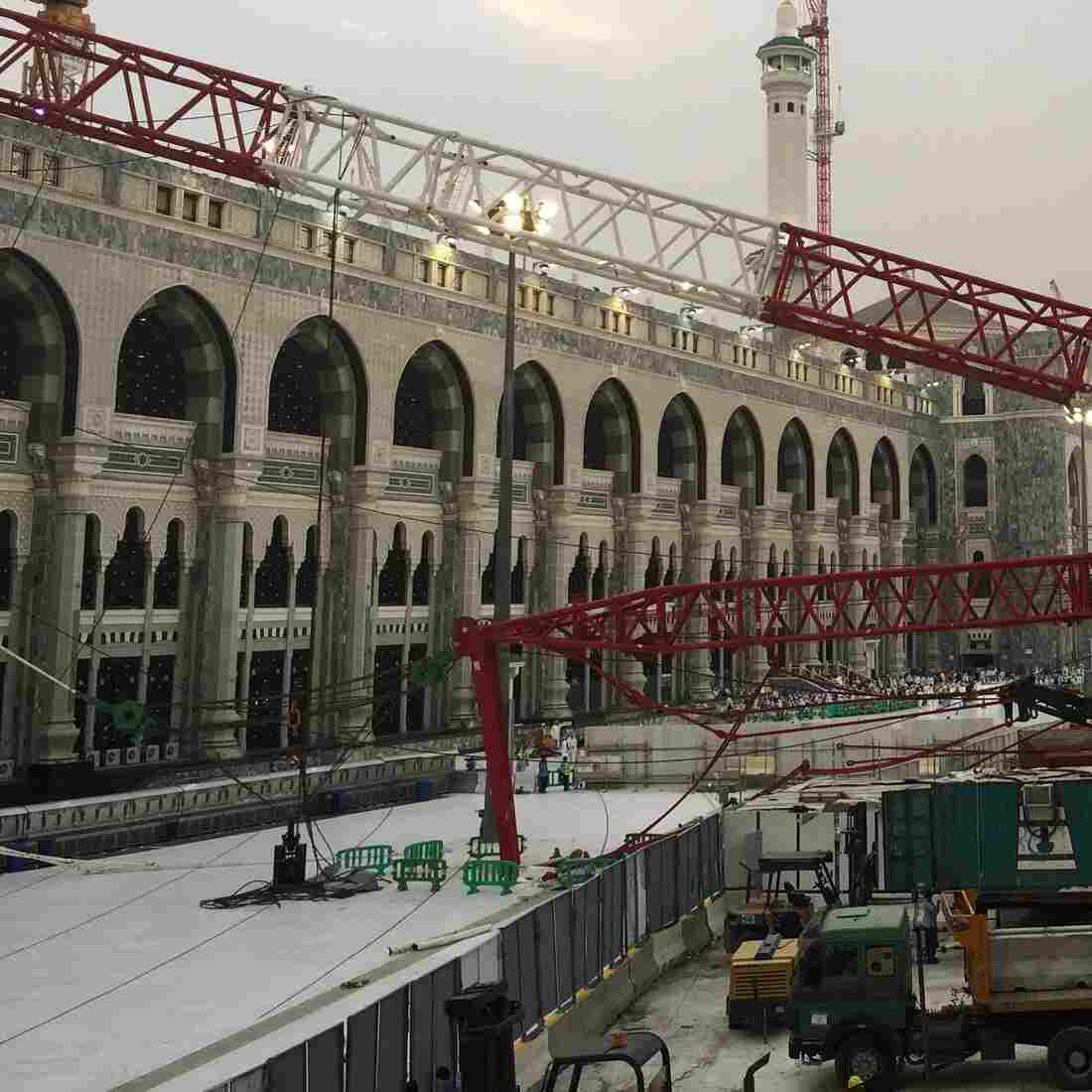 Workers stand next to a collapsed crane that was blamed for 107 deaths at the Grand Mosque in Saudi Arabia's holy Muslim city of Mecca last week.
