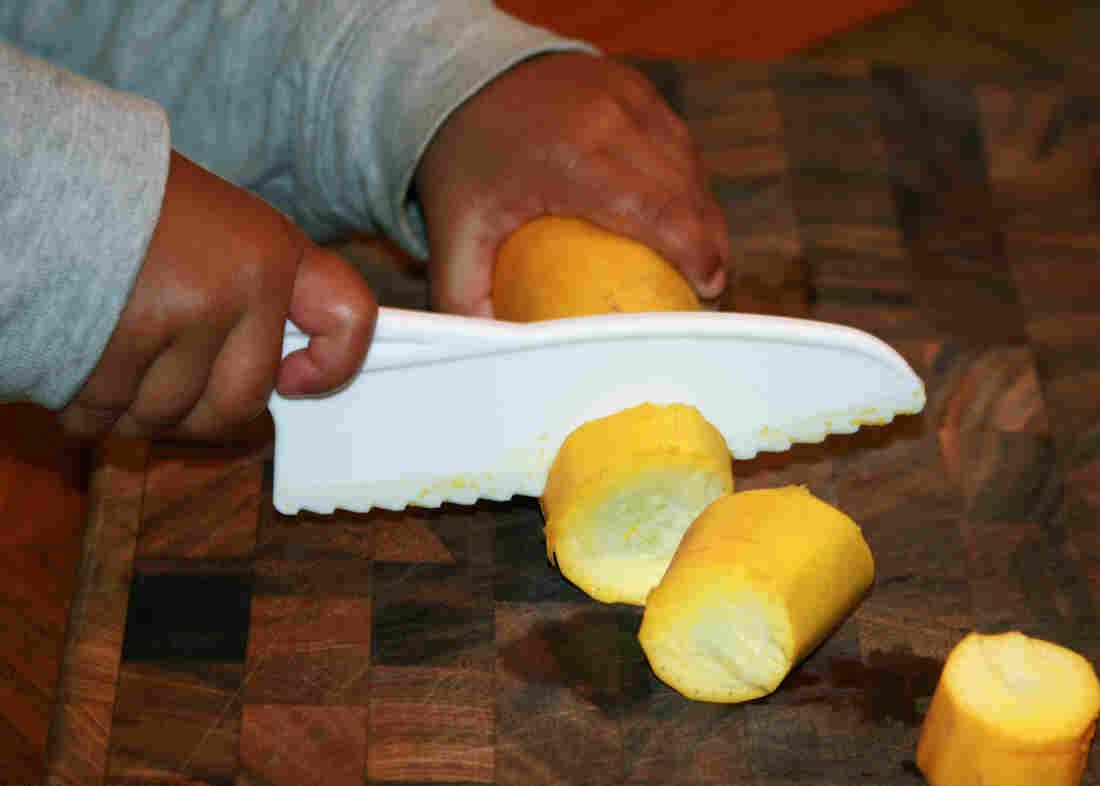 Eka Gupta Goodenough, 3, the author's son, uses a starter knife to chop yellow squash.