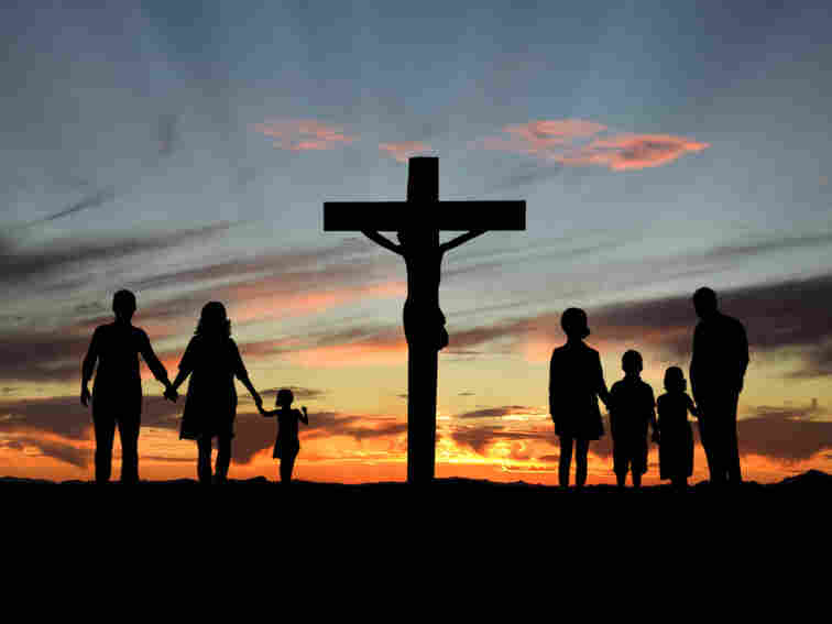 Religious families stand by a cross.