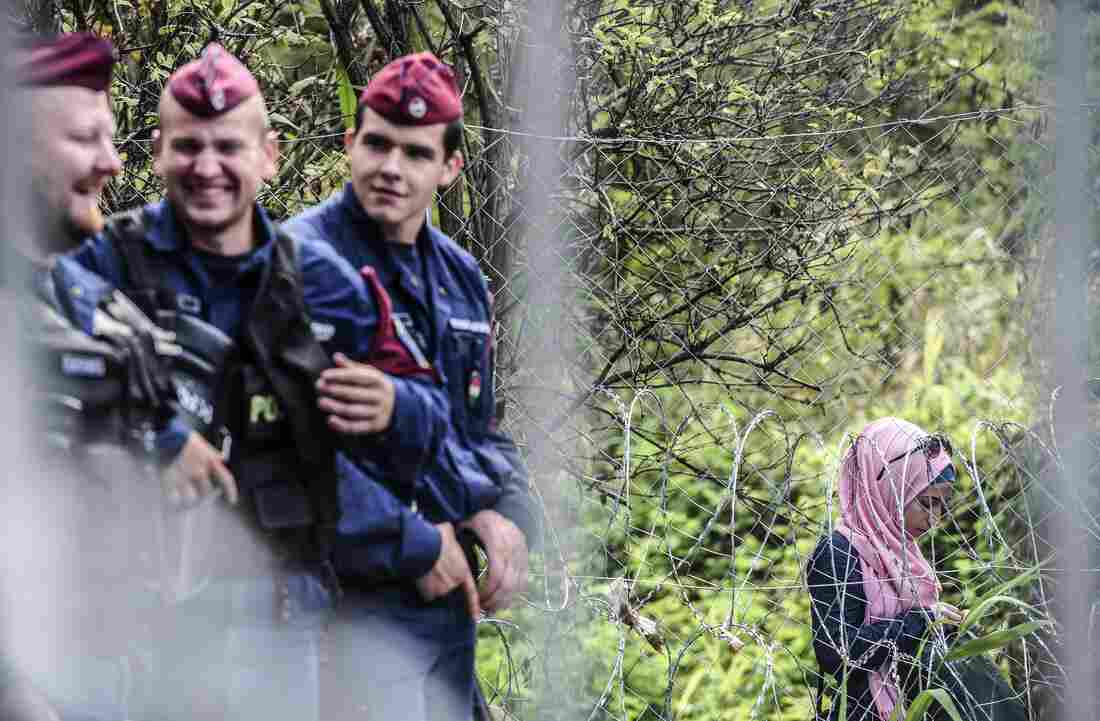 Hungarian border police talk next to a fence, next to a woman who is among hundreds of refugees and migrants caught behind a fence at the Hungarian border with Serbia Wednesday.