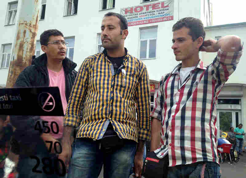 Omar (center) and Alhees (right) camped out for days outside a strip mall and hotel in a rundown part of Budapest, after Hungarian authorities kicked them out of Keleti station. The hotel would not admit them.
