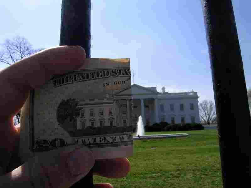 A man holds a $20 bill up in front of the White House.