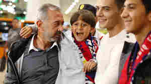 Osama Abdul Mohsen (left) has the promise of a new job in Spain, where soccer officials invited him to come live. He's seen here with his son Zaid as they arrive at the Barcelona train station Wednesday.