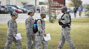 Soldiers walk past a military police officer (right) patrolling the perimeter of the U.S. Army IMCOM HQ building at Fort Sam Houston, Texas, prior to the Article 32 preliminary hearing to determine whether Army Sgt. Bowe Bergdahl will be court-martialed.