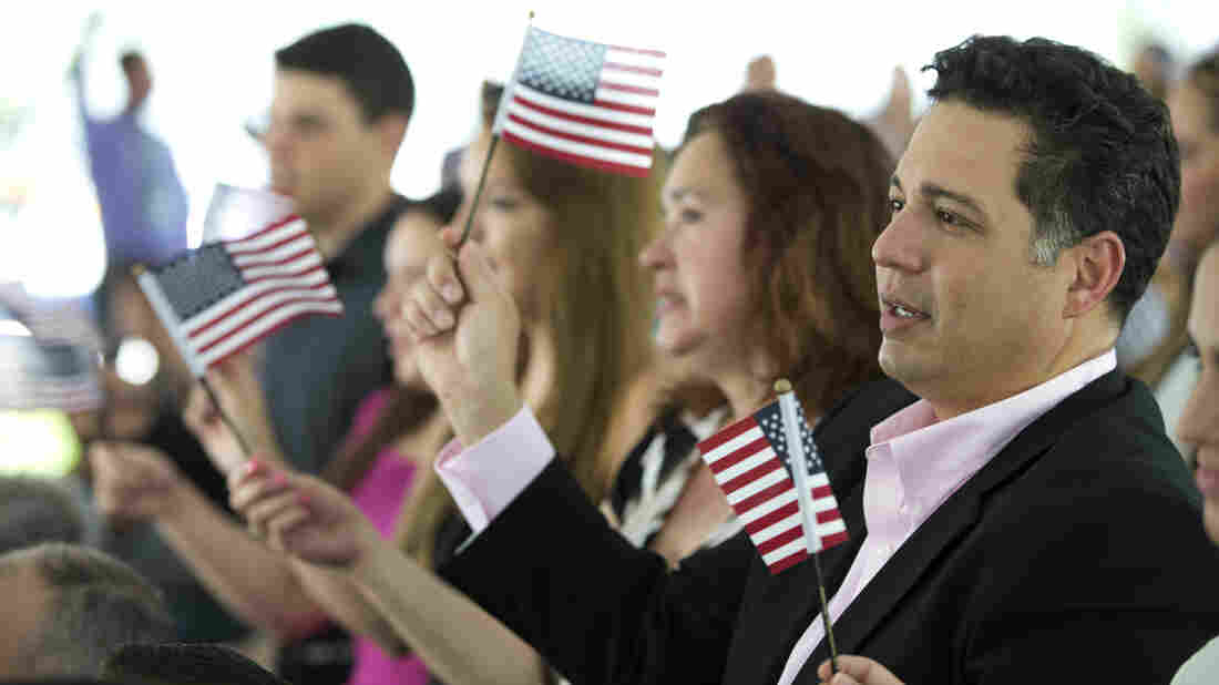 New citizens wave American flags during a U.S. Citizenship and Immigration Services naturalization ceremony in Miami in July.