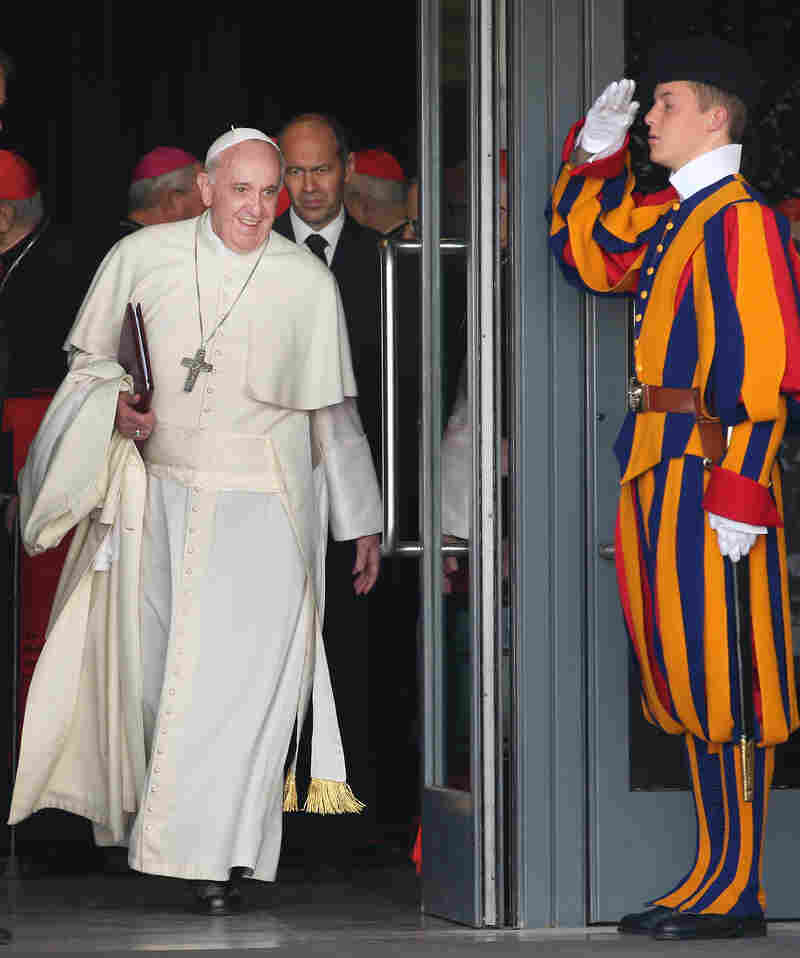 Compared with a Swiss Guard's get-up, the everyday wear of Pope Francis — shown here in the Vatican in 2014 — is downright plain.