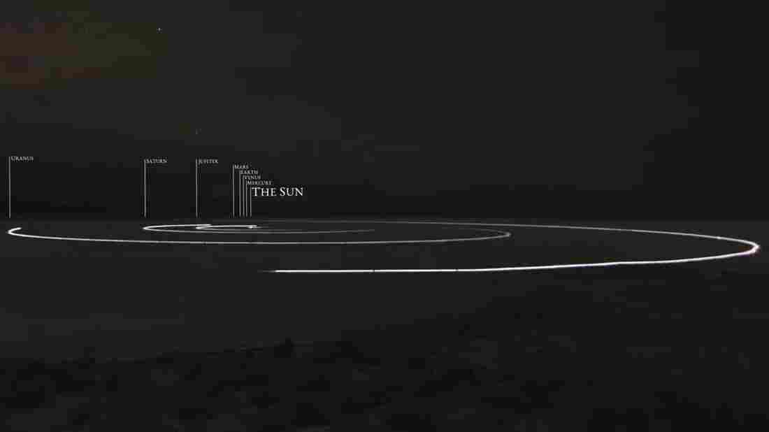 A still image from a video produced by the To Scale Series shows a model of the solar system in which planets orbit the sun on a dry lakebed in Nevada.