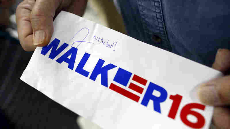 A supporter displays an autographed sticker for Walker at a town hall.
