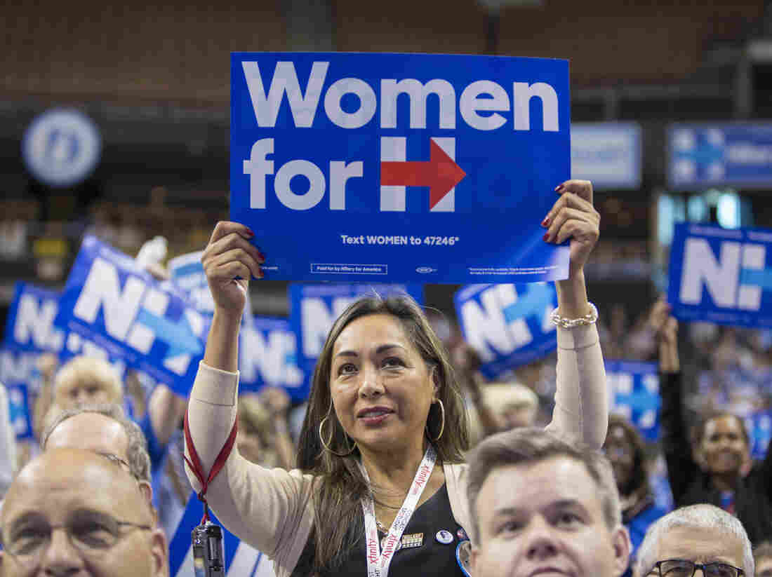 """A supporter holds up a """"Women for H"""" sign while Hillary Clinton speaks at the New Hampshire Democratic Party Convention last weekend in Manchester. When Clinton ran eight years ago, she downplayed the potential historical significance of her candidacy. This time around, she has made so-called women's issues centerpieces of her campaign."""