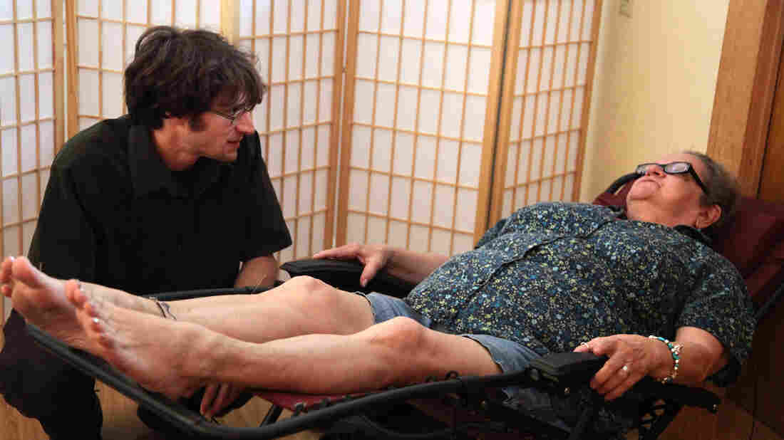 Doris Keene (right) talks with her acupuncturist before a treatment at Portland's Quest Center for Integrative Health. Keene says the treatments have eased her chronic back pain at least as effectively as the Vicodin and muscle relaxants she once relied on.