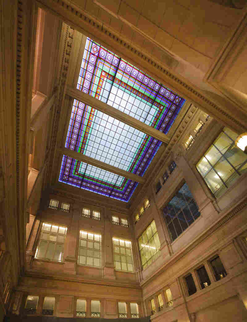The multistory central hall has a stained-glass ceiling, echoed in smaller stained-glass windows throughout the building.