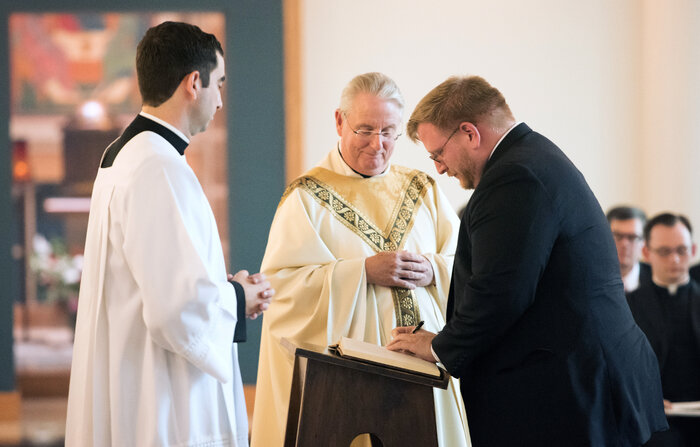 The Rev. Phillip Brown, center, watches as Tom Lawrence, right, a first-year pre-theologian at Theological College, signs the Book of Inscription during the school's opening Mass in August. (Courtesy of The Catholic University of America)