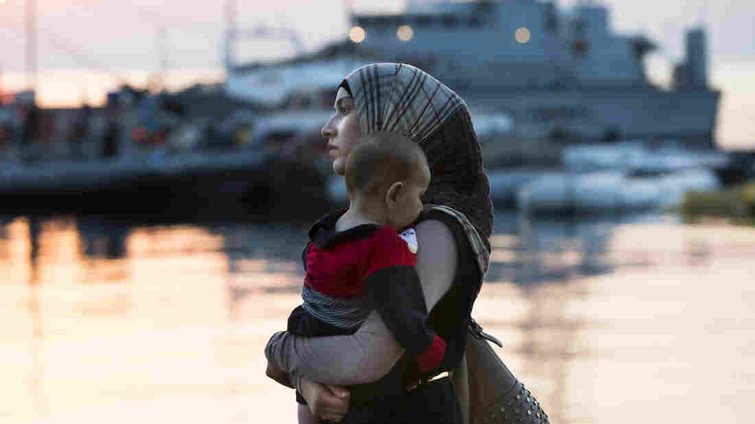 A Syrian refugee woman walks to the ferry Eleftherios Venizelos, which functions as a registration center and accommodation for migrants and refugees on the Greek island of Kos, on Aug. 17. The Islamic State has released multiple videos calling on refugees to return to Syria.