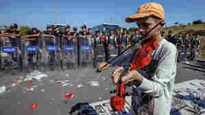 A refugee boy plays a violin as hundreds of migrants are blocked from marching down a highway toward Turkey's western border with Greece and Bulgaria on Saturday. Turkey has some 2 million refugees, mostly from Syria, but says they will not be allowed to settle permanently in the country.