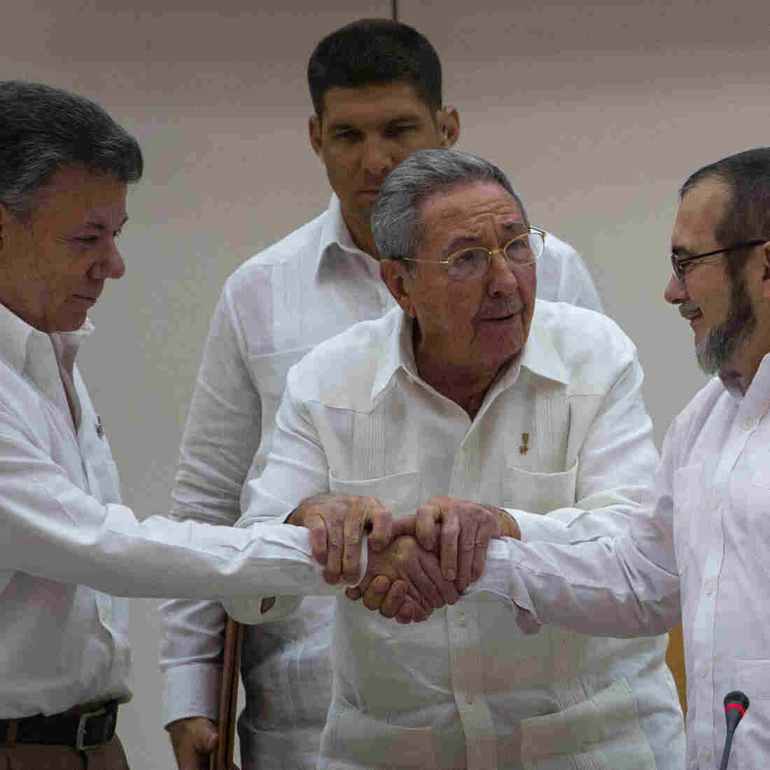 Cuba's President Raul Castro (center) encourages Colombian President Juan Manuel Santos (left) and the commander of the Revolutionary Armed Forces of Colombia or FARC, known as Timochenko, to shake hands, in Havana, Cuba, Wednesday.