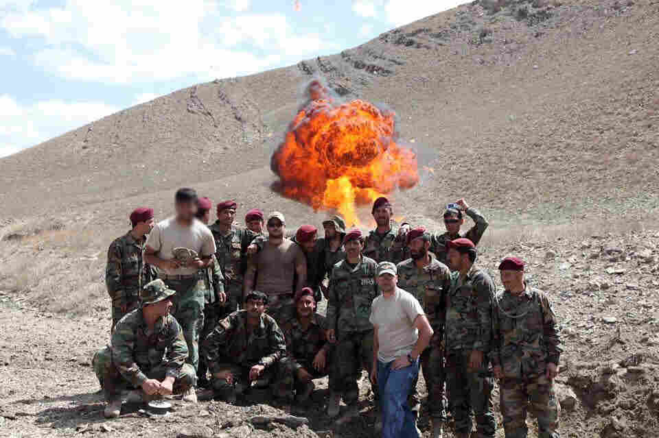 AK, in a tan T-shirt on the left, his face blurred for his protection, was an Afghan interpreter who worked for the U.S. military. He poses with Afghan commandos in front of a controlled explosion. AK worked closely with American Jonathan Schmidt, in the dark tan shirt and a baseball cap (in the center). AK was with Schmidt when he was killed in a 2012 firefight. AK is now seeking a U.S. visa.