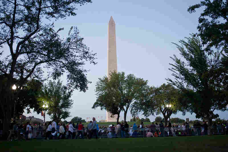 Spectators claim their spots along the papal parade route, with the Washington Monument as a backdrop.