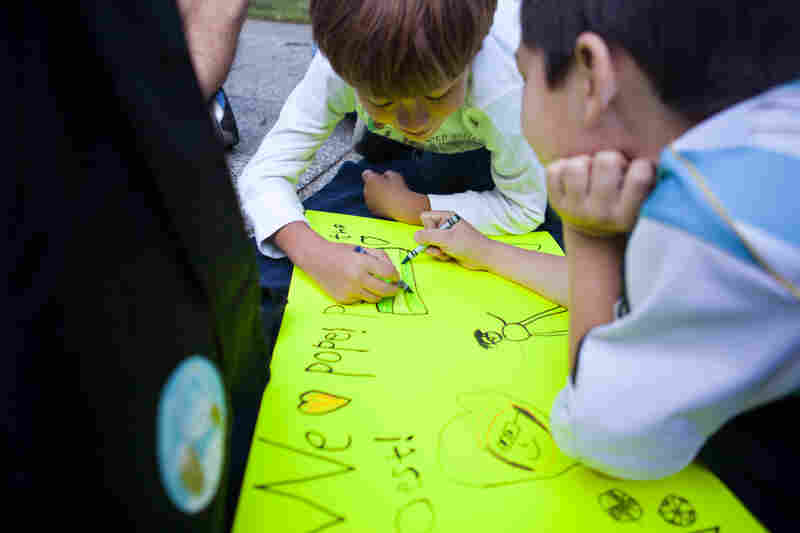 Seven-year-olds Lucas Jefferson (center) and Rafael Xeleya draw on a poster for Pope Francis while waiting for the parade to start.