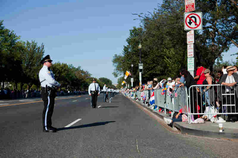 Security keeps spectators off the parade route on Constitution Avenue before the papal parade begins.