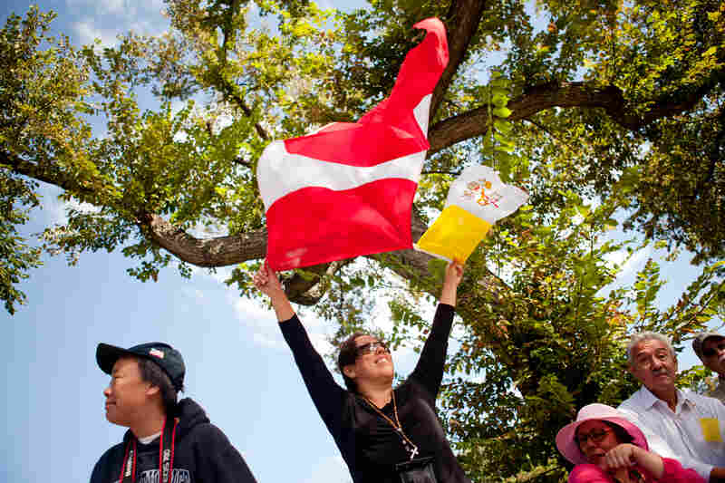 "Patricia Briceno raises the Peruvian and Vatican flags on Constitution Avenue. ""Peru is with him, and we love him,"" said Briceno, who is Peruvian."