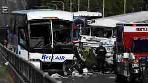 A medical examiner checks the scene of a crash between a tour bus and a tourist duck boat on the Aurora Bridge in Seattle, Wash.