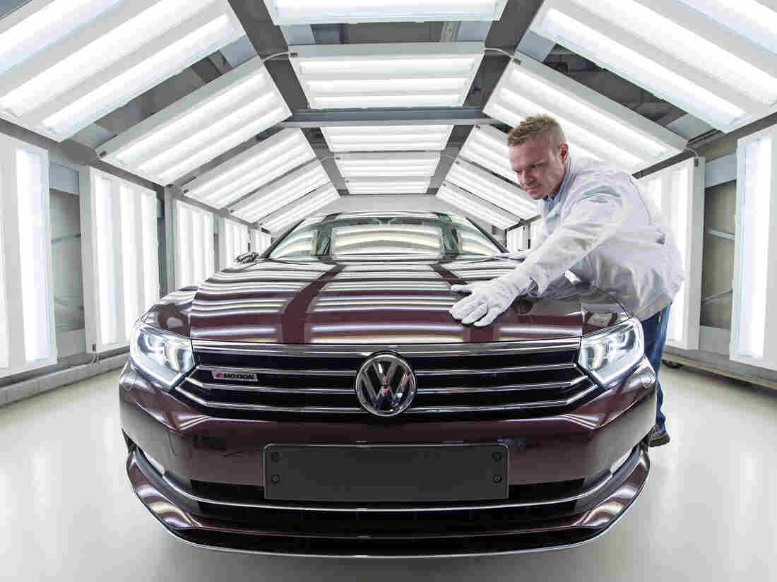 A worker checks a Passat Variant during a press tour at the plant of the German manufacturer Volkswagen Sachsen in Zwickau, Germany.