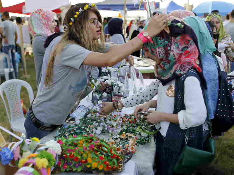 Women make flower garlands at the carnival. This year's theme is diversity, to encourage Iraqis to overcome sectarianism.