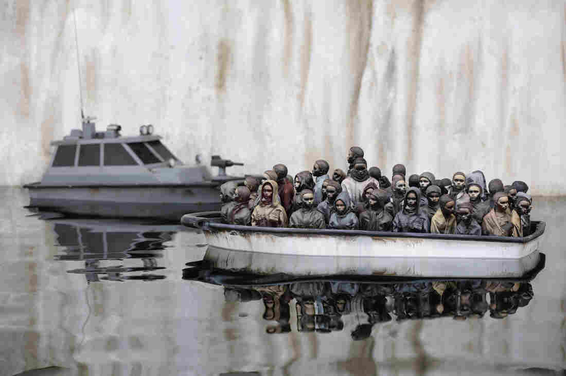 """This art exhibit shows a boat packed with migrants floating in a pond at Banksy's """"bemusement park"""" called Dismaland. Now, the park is being dismantled and the materials are being sent to a refugee camp in France to be used for building shelters."""
