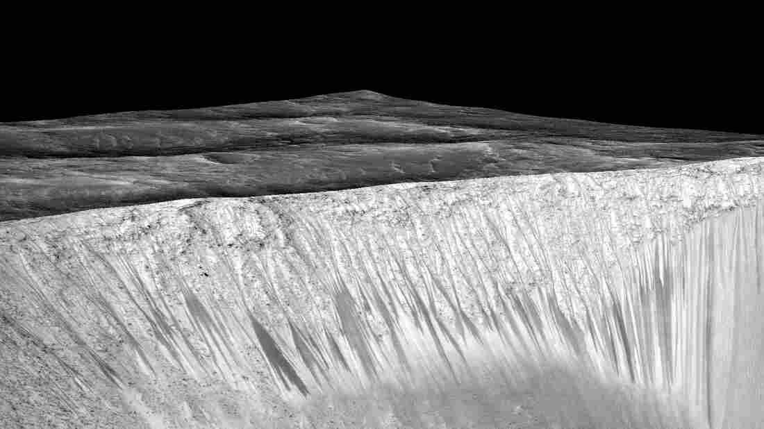 Streaks a few hundred feet in length appear on the walls of Garni crater on Mars. Scientists suspect they are formed by the flow of briny, liquid water.