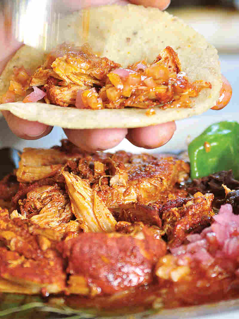 """The name of these tacos, """"cochinita pibil,"""" tells you what's inside: young pig cooked in an oven pit. It's a traditional Mayan dish that originated after the Spanish conquistadors arrived, bringing pigs with them."""