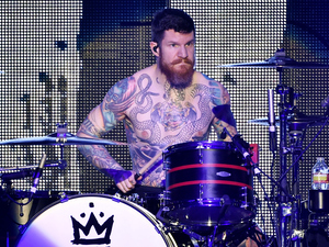 Fall Out Boy drummer Andy Hurley pauses mid-performance to marvel at his own impressive tats.