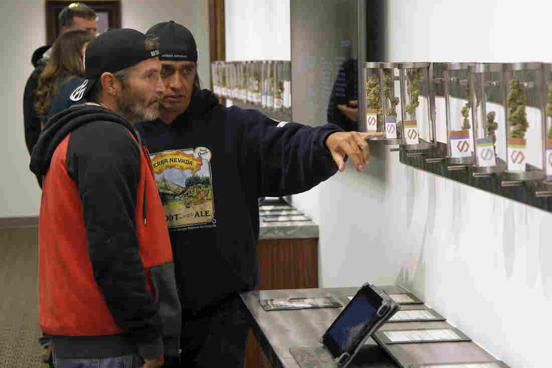 Customers browse samples at Shango Cannabis shop, after the first day of legal recreational marijuana sales began at midnight in Portland, Ore., Thursday.