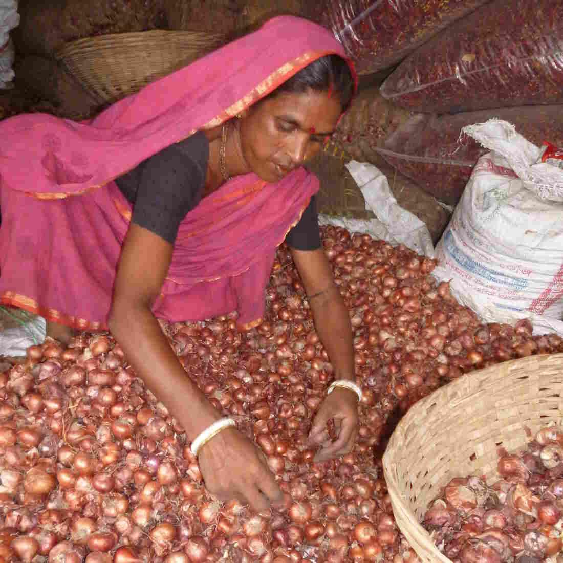 Kamala Rani sorts vegetables at the market in Kapasia, Bangladesh.