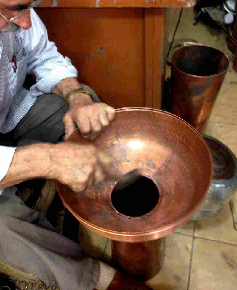 Mahmut Efeoglu works in his shop in the Trabzon copper market. The 70-year-old used to emphasize kitchenware — traditional copper pans, bowls and cups — but has branched out to making decorative copper minarets because the demand for copper cookware has diminished.
