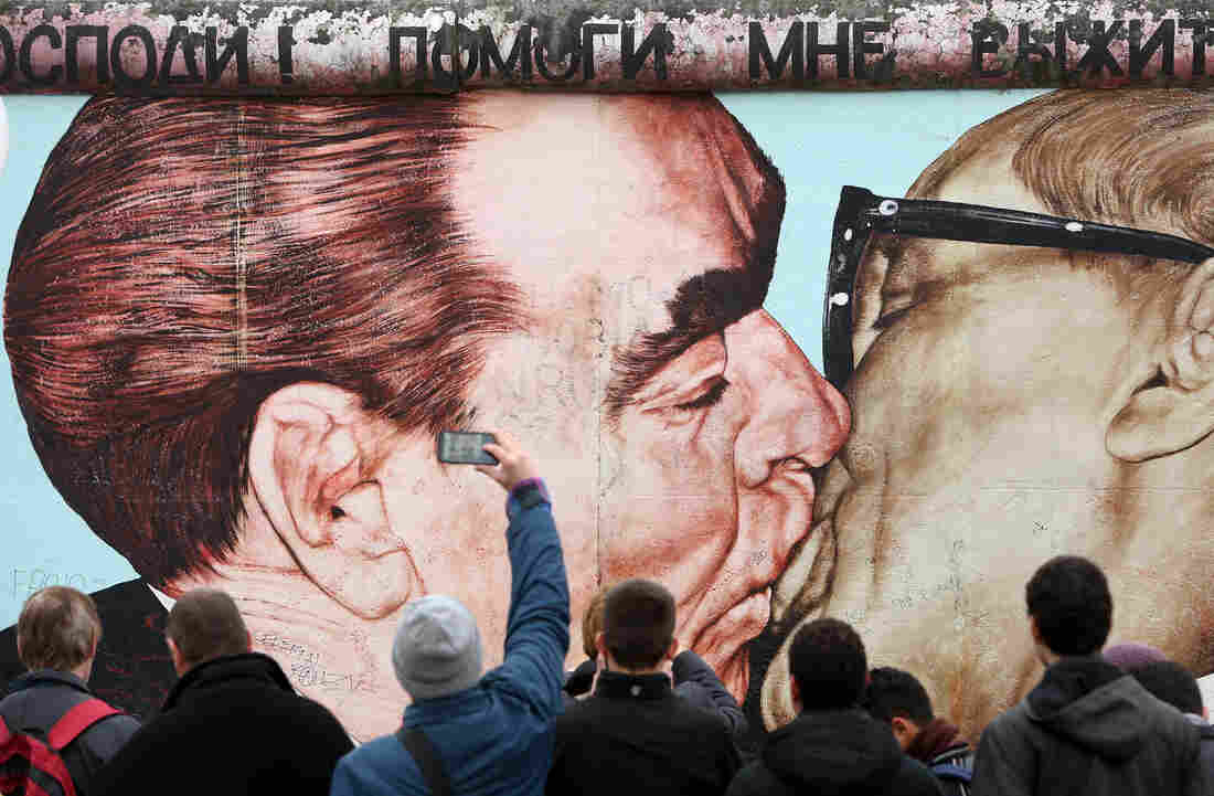 """Dmitri Vrubel's painting of the Soviet Union's Leonid Brezhnev and East Germany's Erich Honecker kissing — under a Russian phrase that reads, """"My God, Help Me to Survive This Deadly Love"""" — is a popular part of the East Side Gallery."""