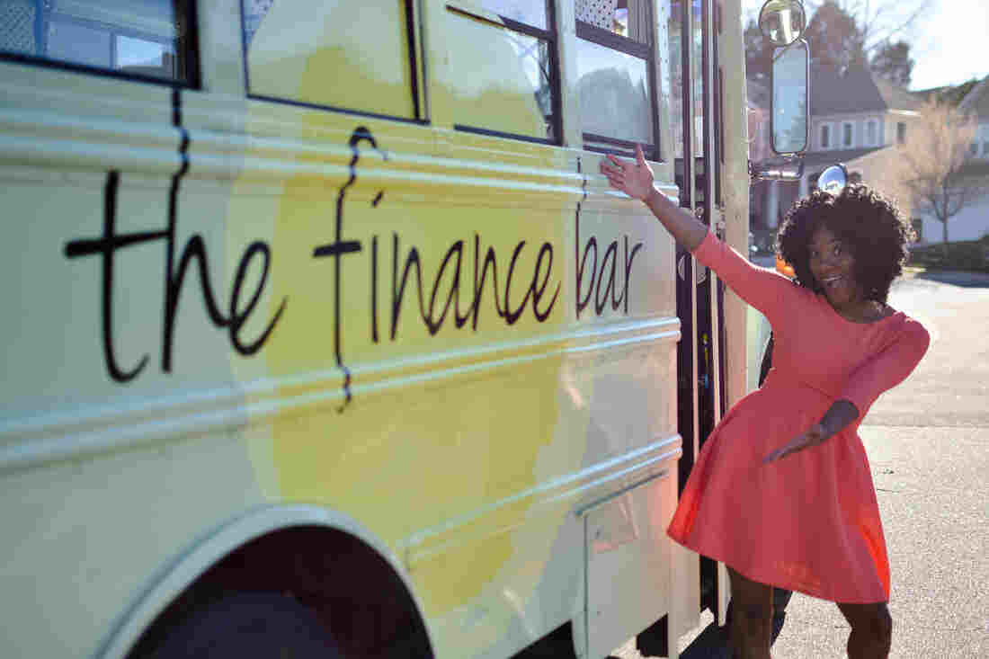 Marsha Barnes shows off the bus that makes the Finance Bar possible.