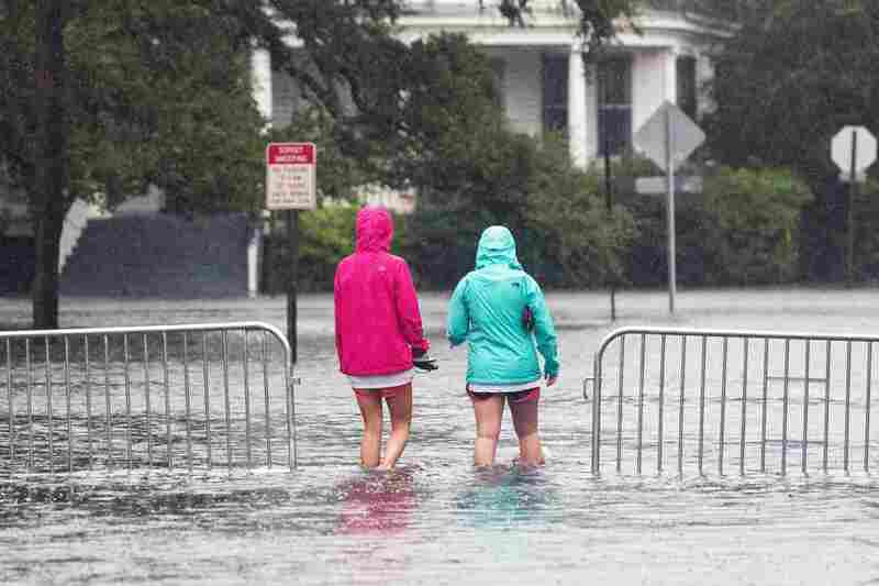Residents walk through floodwaters in the historic district of Charleston, S.C., as Hurricane Joaquin brings heavy rain, flooding and strong winds as it passes offshore Saturday. Flood warnings and watches were posted in several eastern states where more heavy rainfall was forecast.