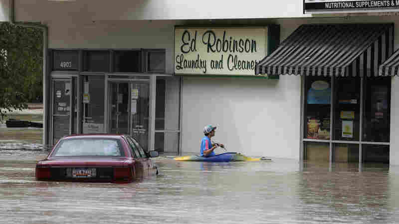 Jordan Bennett, of Rock Hill, S.C., paddles up to a flooded store in Columbia, S.C., on Sunday.