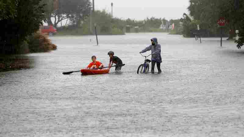 Will Cunningham, 14, rides his bike down Station 29 on Sullivan's Island, S.C., with his friend Patrick Kelly, 14, going the kayak route during flood waters on Sullivan's Island on Saturday.