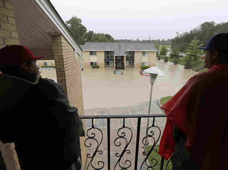 Residents stand on their porch overlooking a flooded apartment building in Columbia, S.C., on Sunday.