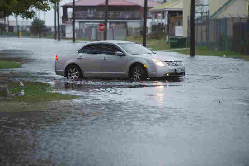 A car drives on flooded Broadway Street in Crisfield, Md., on the Chesapeake Bay early Sunday.