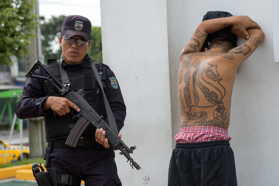 A policeman detains a suspected member of the MS-13 gang at a checkpoint in San Salvador during a ban on public transport imposed by the gangs. (Encarni Pindado for NPR)