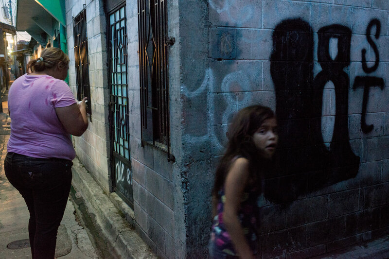 Mother and daughter hang around the streets of a residential area in San Salvador controlled by the gang Barrio 18. (Encarni Pindado/for NPR)