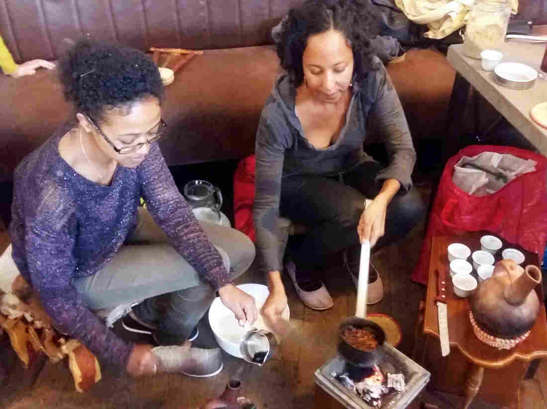 Luwam Melake (left), a recently arrived Eritrean refugee, and Saba Tesfay, who is half-Hungarian and half-Eritrean, wash, roast and grind coffee beans during a traditional Eritrean coffee ceremony. They performed the ceremony at the Kisuzem restaurant as part of a Budapest food festival celebrating the cuisine from Syria, Afghanistan, Eritrea and Somalia.