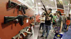People examine rifles on display at the annual National Rifle Association convention in Nashville, Tenn., in April.