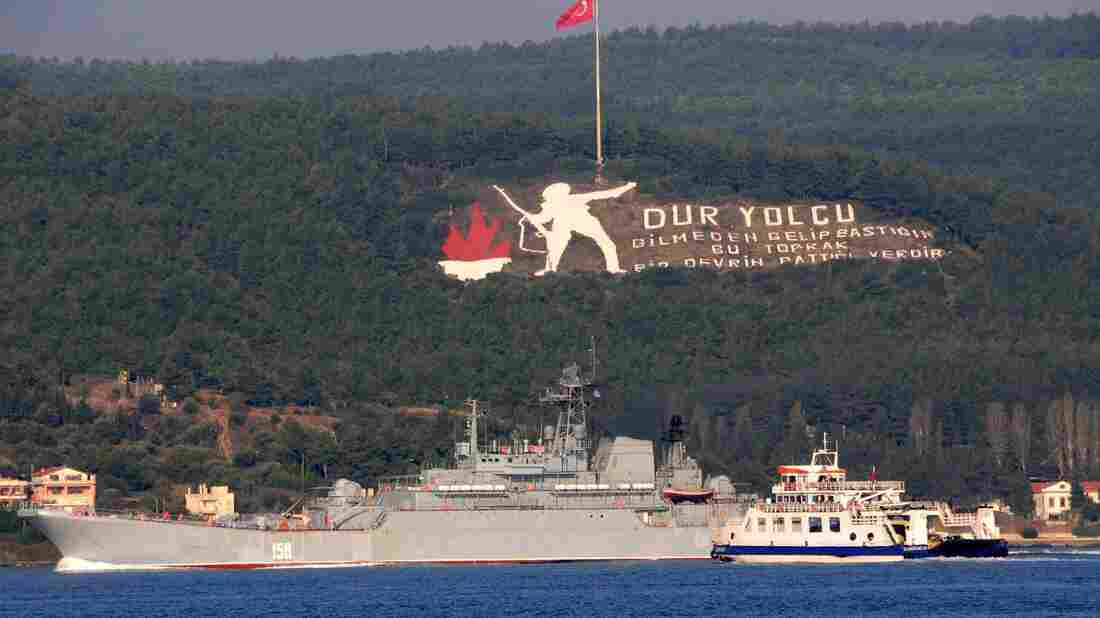 "The Russian naval ship Caesar Kunikov passes through the Dardanelles strait in Turkey to the Mediterranean Sea on Sunday. The memorial on the mountain commemorates the World War I Gallipoli campaign, with a sign citing a Turkish poem: ""Stop passenger. The land you come upon without knowing is the place an era had ceased."" Russia began launching military operations in Syria last Wednesday."