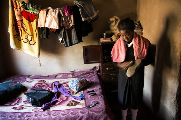 Madalitso Mulando brushes off her shoes before heading to school in Lusaka, Zambia. Last year, she missed a whole semester while her parents struggled to scrape together tuition. (Samantha Reinders for NPR)
